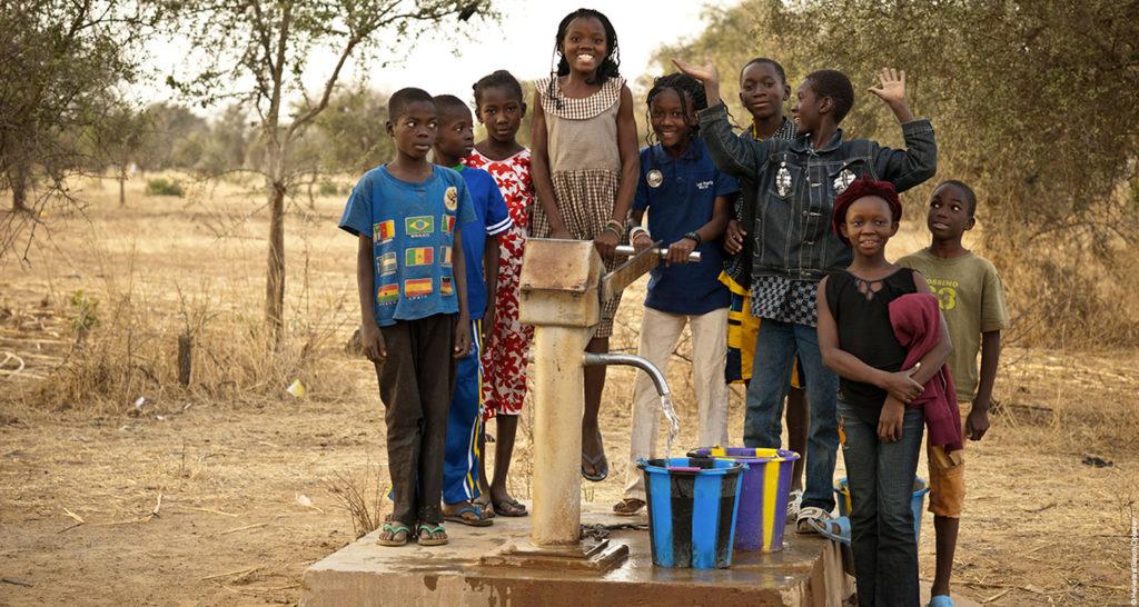 Kinder um einen neu gebauten Brunnen.